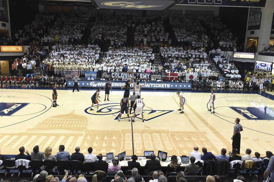 In this Nov. 16, 2015 photo provided by The George Washington University, George Washington plays Virginia in front of a sold out crowd at an NCAA college basketball game at the Charles E. Smith Center in Washington, DC. College basketball floors once had simple designs, the only flair usually the addition of color in the lane or at midcourt. Court designs have taken a creative twist over the past few years with schools adding elaborate detail. (The George Washington University via AP) **FILE**