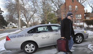 In his Jan. 26, 2017, photo, Happy Cab driver Bill Mulloy carries a customer's bag to the door as he delivered them home in central Lincoln, Neb. According to statistics compiled by the state's Public Service Commission, the numbers of taxis, drivers and rides have plummeted over the past six years in the Capital City while generally growing in Omaha and other parts of the state. (Eric Gregory/The Journal-Star via AP)