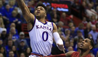 Kansas guard Frank Mason III (0) scores while covered by Iowa State guard Monte Morris (11) during the first half of an NCAA college basketball game in Lawrence, Kan., Saturday, Feb. 4, 2017. (AP Photo/Orlin Wagner)