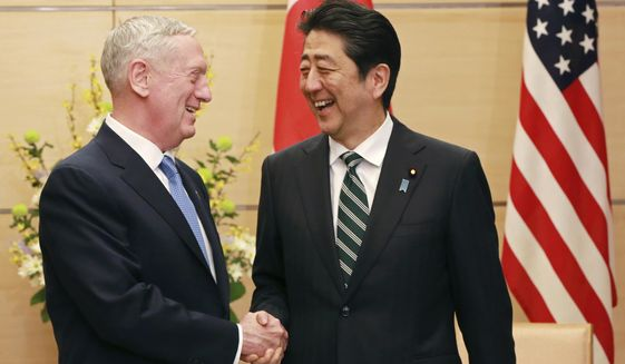 """U.S. Defense Secretary Jim Mattis, left, and Japanese Prime Minister Shinzo Abe, right, shake hands at the prime minister's office in Tokyo, Friday, Feb. 3, 2017.  In an explicit warning to North Korea, U.S. Defense Secretary Mattis on Friday said any use of nuclear weapons by the North on the United States or its allies would be met with what he called an """"effective and overwhelming"""" response. (AP Photo/Eugene Hoshiko, Pool)"""