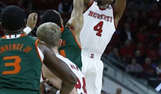 N.C. State's Dennis Smith Jr. (4) makes a three-pointer as time runs out in the first half as Miami's Bruce Brown (11) defends during the first half of N.C. State's game against Miami at PNC Arena in Raleigh, N.C., Saturday, Feb. 4, 2017.  (Ethan Hyman/The News & Observer via AP)