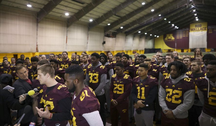 FILE - In this Dec. 15, 2016, file photo, Minnesota wide receiver Drew Wolitarsky, flanked by quarterback Mitch Leidner, obscured behind Wolitarsky, and tight end Duke Anyanwu gestures as he stands in front of other team members while talking to reporters in the Nagurski Football Complex in Minneapolis. The University of Minnesota panel that heard the case of alleged involvement by 10 football players in a sexual assault on campus has upheld recommended punishment for five of them and overturned or reduced discipline for the other half. In December, players threatened to boycott the team's Holiday Bowl game. (Jeff Wheeler/Star Tribune via AP, File)