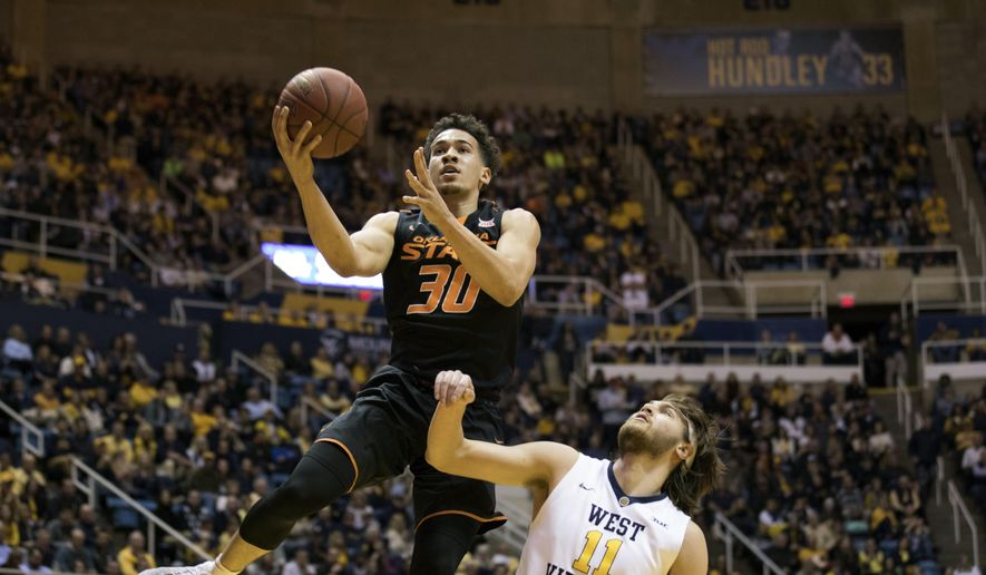 Oklahoma State guard Jeffrey Carroll (30) drives to the basket in the first half of an NCAA college basketball game against West Virginia Saturday, Feb. 4, 2017, in Morgantown, W. Va.  (AP Photo/Walter Scriptunas II)