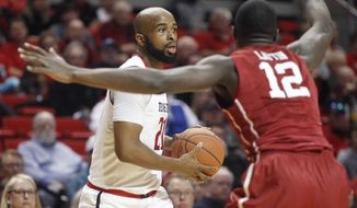 Texas Tech forward Anthony Livingston looks for a teammate to pass to while defended by Oklahoma forward Khadeem Lattin during the first half of an NCAA college basketball game Saturday, Feb. 4, 2017, in Lubbock, Texas. (Mark Rogers/Lubbock Avalanche-Journal via AP)