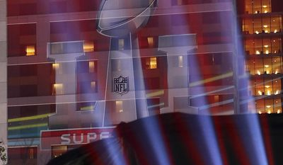 A image of the Lombardi Trophy is projected on the side of a building during Super Bowl Live in Discovery Green park on Thursday, Feb. 2, 2017, in Houston.  (Curtis Compton/Atlanta Journal-Constitution via AP)   /Atlanta Journal-Constitution via AP)