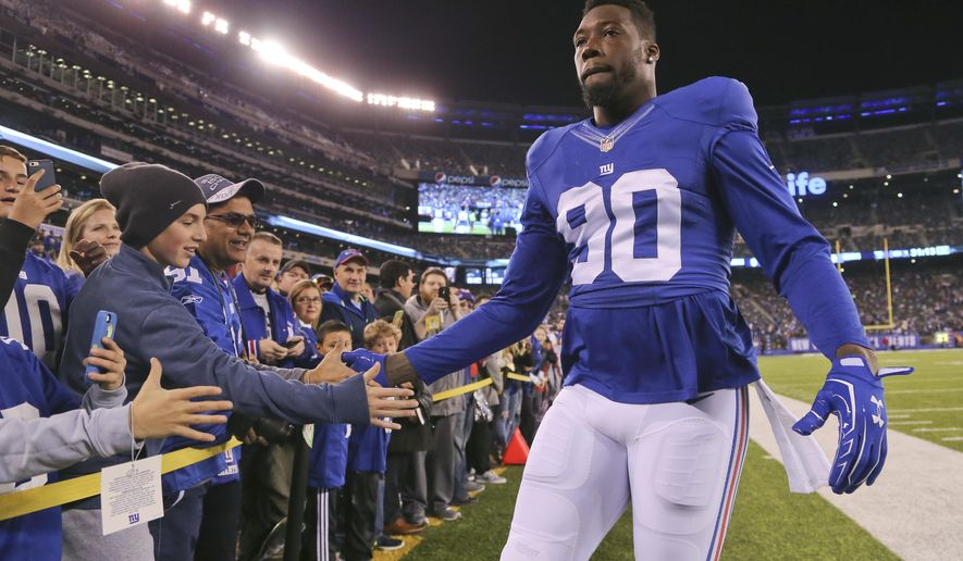 FILE - In this Nov. 14, 2016, file photo, New York Giants defensive end Jason Pierre-Paul (90) greets fans before an NFL football game against the Cincinnati Bengals, in East Rutherford, N.J.    Pierre-Paul and ESPN have settled a lawsuit over the network's disclosure of his medical records from a 2015 fireworks accident. ESPN announced the settlement on Friday, Feb. 4, 2017,  saying it believes that the network's reporting about the injury was newsworthy and journalistically appropriate. (AP Photo/Seth Wenig, File)