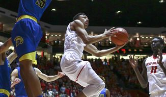 New Mexico's Elijah Brown (4) drives to the basket while guarded by San Jose State's Brandon Clarke (15), as New Mexico's Obij Aget (11) watches during the first half of an NCAA college basketball game in Albuquerque, N.M., Saturday, Feb. 4, 2017. (AP Photo/Juan Antonio Labreche)