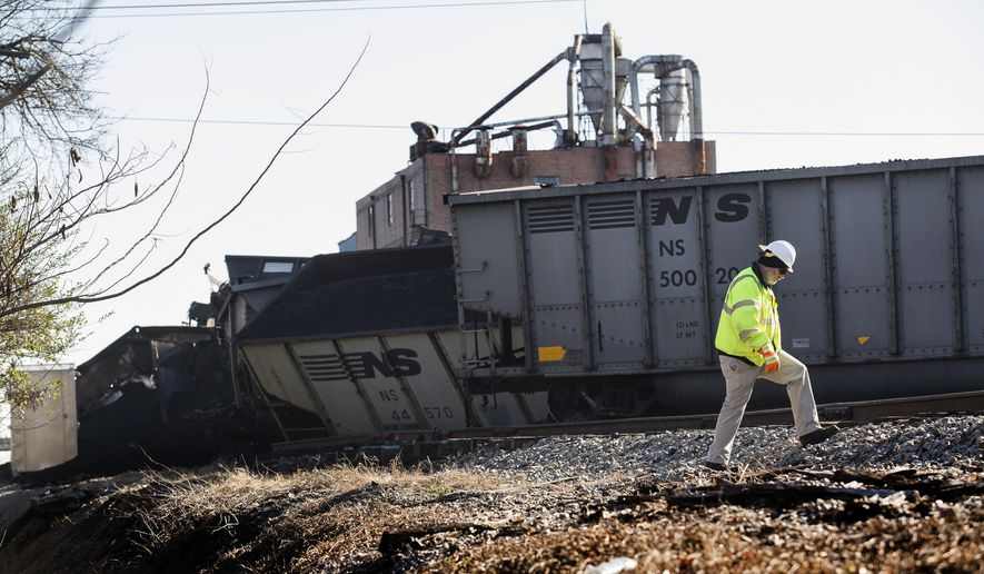 A workers for Norfolk Southern walks at the scene of a multi-car coal train derailment near downtown Suffolk, Va., Saturday morning, Feb. 4, 2017. (Bill Tiernan/The Virginian-Pilot via AP)