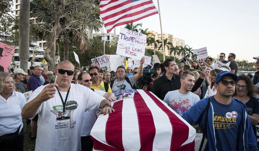 """Protesters push a casket representing the """"Death of Democracy"""" down Flagler Drive in West Palm Beach, Fla. as President Donald Trump and his wife, Melania, attend the 60th annual Red Cross Ball at Mar-a-Lago on Saturday Feb. 4, 2017. (Michael Ares/The Palm Beach Post via AP)"""