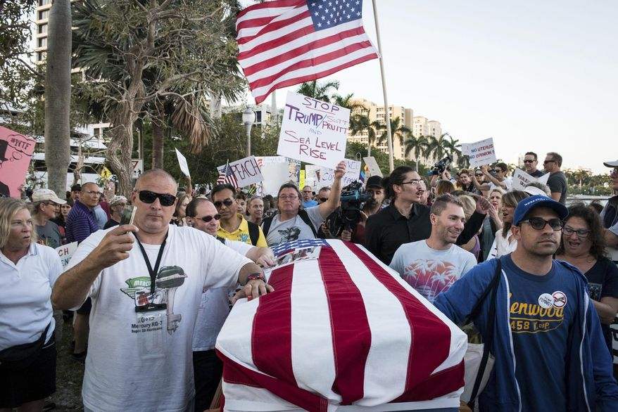 "Protesters push a casket representing the ""Death of Democracy"" down Flagler Drive in West Palm Beach, Fla. as President Donald Trump and his wife, Melania, attend the 60th annual Red Cross Ball at Mar-a-Lago on Saturday Feb. 4, 2017. (Michael Ares/The Palm Beach Post via AP)"