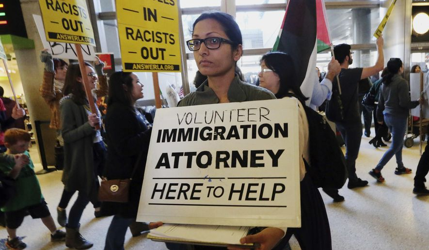 A woman offers legal services at the customs arrival area as demonstrators opposed to President Donald Trump's executive orders barring entry to the U.S. by Muslims from certain countries march behind at the Tom Bradley International Terminal at Los Angeles International Airport on Saturday, Feb. 4, 2017. (AP Photo/Reed Saxon)