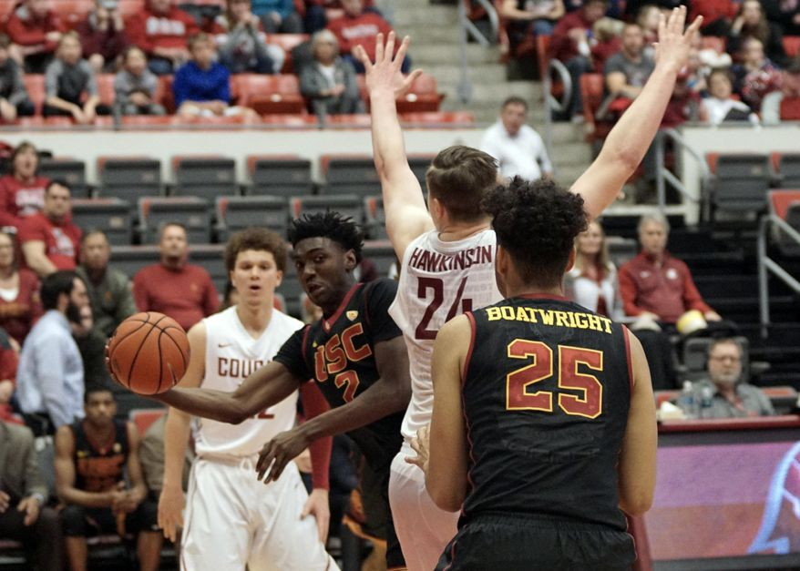 Southern California guard Jonah Mathews (2) passes to Beenie Boatwright (25) behind the back of Washington State forward Josh Hawkinson (24) in the first half of an NCAA college basketball game, Saturday, Feb. 4, 2017, in Pullman, Wash. (AP Photo/Kai Eiselein)