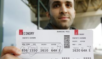 Iranian-born bioengineer researcher Nima Enayati holds up his boarding pass at the Milan's Malpensa International airport in Busto Arsizio, Italy, Sunday, Feb. 5, 2017. Just hours after an appeals court blocked an attempt to re-impose the travel ban, Iranian researcher Nima Enayati checked in on an Emirates Airline flight direct from Milan's Malpensa airport to New York's JFK on Sunday afternoon. (AP Photo/Antonio Calanni)