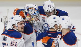 Edmonton Oilers players celebrate with goaltender Cam Talbot after beating the Montreal Canadiens in an NHL hockey game in Montreal on Sunday, Feb. 5, 2017. (Graham Hughes/The Canadian Press via AP)