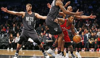 Toronto Raptors guard Kyle Lowry (7) gets caught between Brooklyn Nets forward Rondae Hollis-Jefferson, second from left, and guard Randy Foye (2) as Nets center Brook Lopez (11) watches the perimeter during the first half of an NBA basketball game, Sunday, Feb. 5, 2017, in New York. (AP Photo/Kathy Willens)