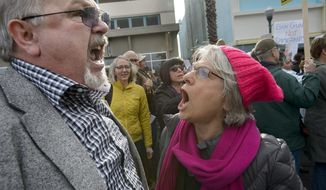 President Donald Trump supporter Lance Snead, of Roseville, Calif., left, is confronted by an anti-Trump supporter Louise Isaacson, of Newcastle, Calif., during a rally in front of the Tower Theatre in Roseville on Saturday, Feb. 4, 2017. Snead said although he was invited to Republican Congressman Tom McClintock's town hall meeting, he was not allowed into the theater. (Randall Benton/The Sacramento Bee via AP)