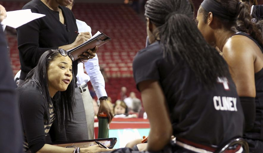 South Carolina's head coach Dawn Staley, left, talks to her players during a timeout in the second half of an NCAA college basketball game against Arkansas, Sunday, Feb. 5, 2017, in Fayetteville, Ark. (AP Photo/Samantha Baker)