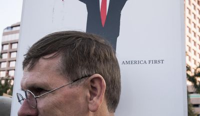 A man protests in front of Trump Plaza holding a sign depicting the cover of the German magazine Der Spiegel in West Palm Beach, Fla. as President Donald Trump and first lady Melania attend the 60th annual Red Cross Ball at Trump's Mar-a-Lago resort on Saturday, Feb. 4, 2017. (Michael Ares/Palm Beach Post via AP)