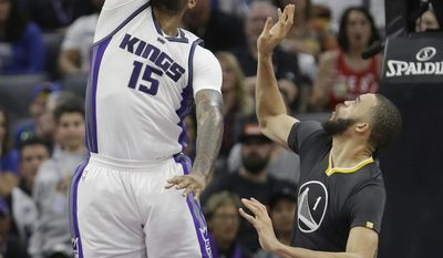 Sacramento Kings forward DeMarcus Cousins, left, dunks over Golden State Warriors center JaVale McGee during the first half of an NBA basketball game Saturday, Feb. 4, 2017, in Sacramento, Calif. (AP Photo/Rich Pedroncelli)