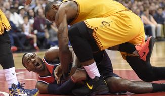 Cleveland Cavaliers forward LeBron James, top, battles for the ball against Washington Wizards guard John Wall, bottom, during the second half of an NBA basketball game, Monday, Feb. 6, 2017, in Washington. The Cavaliers won 140-135 in overtime. (AP Photo/Nick Wass)