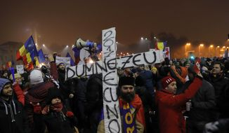 """A man holds a cross that reads: """"God is with us"""" during a protest in Bucharest, Romania, Monday, Feb. 6, 2017. The leader of Romania's ruling center-left coalition said Monday the government won't resign following the biggest demonstrations since the end of communism against a measure that would ease up on corruption. (AP Photo/Vadim Ghirda)"""