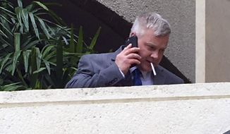 James August uses a cellphone outside the Honolulu federal courthouse Monday, Feb. 6, 2017, after pleading guilty to interfering with a flight crew. He says he doesn't remember what happened on the Hawaiian Airlines flight but doesn't dispute a prosecutor's account that his threatening and aggressive behavior forced the New York City-bound flight to return to Honolulu. (AP Photo/Jennifer Sinco Kelleher)