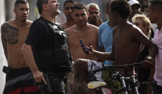 """A Civil Police officer yells """"get back"""" to a crowd calling him out for shooting a minor in the leg who was attempting to loot an electronic store, in Vitoria, Espirito Santo state, Brazil, Monday, Feb 6, 2017. Protests by the friends and family of military police in Espirito Santo have led to an increase in crime and forced the shut-down of some state services, authorities said Monday. The protests calling for higher pay began this weekend outside barracks throughout the small, coastal state and have prevented vehicles from leaving. (AP Photo/Diego Herculano)"""