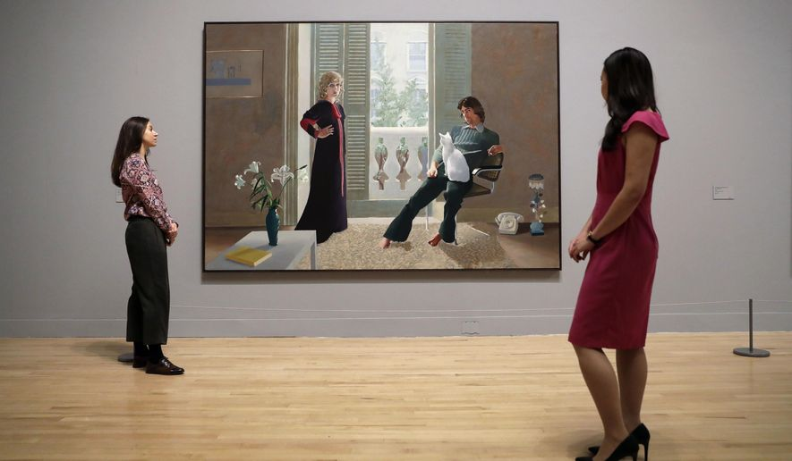 """Tate representatives pose for photographs next to British artist David Hockney's """"Mr and Mrs Clark and Percy"""" during a photocall to promote the largest-ever retrospective of his work at Tate Britain gallery in London, Monday, Feb. 6, 2017. The exhibition, which opens to the public from Feb. 9 and runs until May 29, celebrates the 79-year-old's achievement in painting, drawing, photography and video. (AP Photo/Matt Dunham)"""