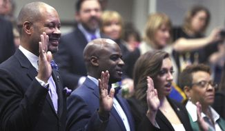 Senate Majority Leader Aaron Ford, D-Las Vegas, left, takes the oath of office with his fellow State Senators in Carson City, Nev., on opening day of the Legislative Session, Monday, Feb 6, 2017. (AP Photo/Lance Iversen)