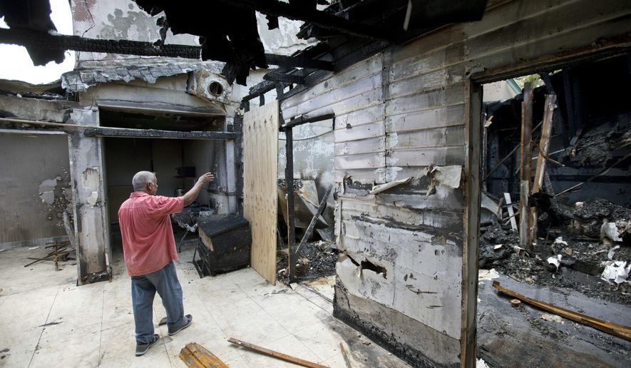 FILE - In a Thursday, Sept. 15, 2016, file photo, Farhad Khan, who has attended the Islamic Center of Fort Pierce for more than seven years, shows members of the media its charred remains, in Fort Pierce, Fla. Joseph Schneider, an ex-convict who investigators say confessed to setting fire to the mosque tied to the Orlando nightclub shooter, pleaded no contest to those charges, Monday, Feb. 6, 2017. (AP Photo/Wilfredo Lee, File)