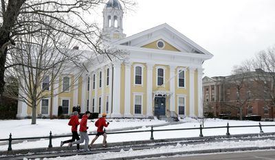 FILE - In this Jan. 14, 2016 file photo, runners make their way along a sidewalk on the campus of Wheaton College in Norton, Mass. The college has created a refugee scholarship in response to President Donald Trump's January 2017 order on immigration and refugees and is calling on other colleges to do the same. (AP Photo/Steven Senne, File)
