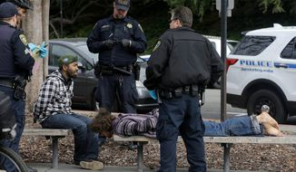 """Police officers arrested two men who attacked a student on the University of California, Berkeley, campus on Thursday. Jack Palkovic, a student wearing a """"Make America Great Again"""" hat, was attacked on the campus a day after violent protests. (Associated Press)"""