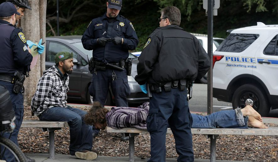 "Police officers arrested two men who attacked a student on the University of California, Berkeley, campus on Thursday. Jack Palkovic, a student wearing a ""Make America Great Again"" hat, was attacked on the campus a day after violent protests. (Associated Press)"