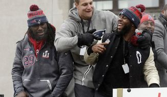 New England Patriots tight end Rob Gronkowski, center, points to running back James White alongside running back LeGarrette Blount, left, during a parade Tuesday, Feb. 7, 2017, in Boston to celebrate the team's 34-28 win over the Atlanta Falcons in Sunday's NFL Super Bowl 51 football game in Houston. White's touchdown in overtime sealed the victory. (AP Photo/Steven Senne)