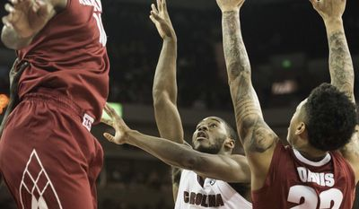 South Carolina guard Justin McKie (20) attempts shoots against Alabama's Shannon Hale (11) and Ar'Mond Davis (22) during the first half of an NCAA college basketball game Tuesday, Feb. 7, 2017, in Columbia, S.C. (AP Photo/Sean Rayford)