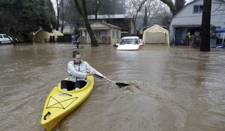 Rachel Turner uses a kayak to access her flooded home Tuesday, Feb. 7, 2017, in Felton, Calif. Flash flood watches are in place for parts of Northern California down through the Central Coast as heavy rains swamp roads and threaten to overtop rivers and creeks. (AP Photo/Marcio Jose Sanchez)