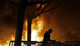 In this Feb. 1, 2017, file photo, a fire set by demonstrators protesting a scheduled speaking appearance by Breitbart News editor Milo Yiannopoulos burns on Sproul Plaza on the University of California, Berkeley campus. (AP Photo/Ben Margot, File)