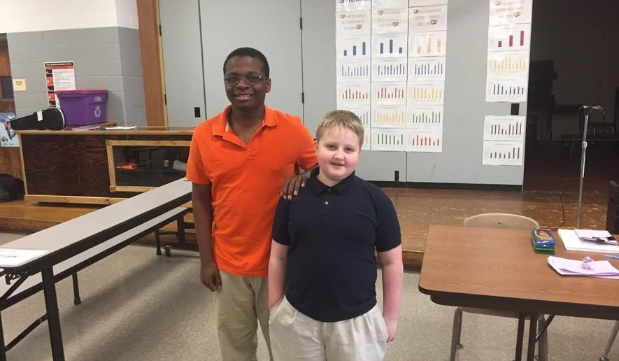 In this Jan. 18, 2017 photo, eighth-grader Elija Cooper left, poses with fifth-grader  Camden Maves after Carl Sandbug Middle School's geography bee in Freeport, Ill. Cooper won the competition and Maves was runner up. (Derrick Mason/The Journal-Standard, via AP)