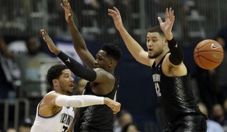 Villanova's Josh Hart, left, pass the ball around Georgetown's L.J. Peak, center, and Bradley Hayes during the first half of an NCAA college basketball game, Tuesday, Feb. 7, 2017, in Villanova, Pa. (AP Photo/Matt Slocum)