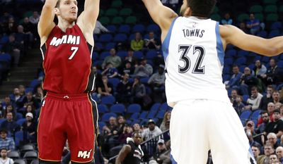 Miami Heat's Goran Dragic, left, of Slovenia, shoots of of his seven game three-point shots over Minnesota Timberwolves' Karl-Anthony Towns during the second half of an NBA basketball game Monday, Feb. 6, 2017, in Minneapolis. The Heat won 115- 113. Dragic led the Heat with 33 points while Towns led the Timberwolves with 35 points. (AP Photo/Jim Mone)