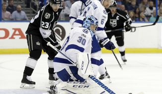 Tampa Bay Lightning goalie Ben Bishop (30) knocks a rebound away from Los Angeles Kings right wing Dustin Brown (23) during the first period of an NHL hockey game Tuesday, Feb. 7, 2017, in Tampa, Fla. Looking on is Lightning defenseman Anton Stralman (6), of Sweden. (AP Photo/Chris O'Meara)