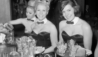 In this Jan. 15, 1963, photo, Playboy Bunnies Elka Hellmann, from left, Monica Schaller and Sabrina Scharf serve drinks at New York's Playboy Club. The tightly corseted Playboy Bunnies, with rabbit tails and ears, will soon be back in business in New York City. Three decades after the original Playboy Club closed in Manhattan, a new club will debut later this year in a hotel a few blocks from Times Square. (AP Photo/John Lent, File)