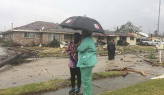 Linda Pierre, left, and April Williams look around the east New Orleans neighborhood after a tornado touchdown, Tuesday, Feb. 7, 2017. At least three tornados touchdown causing damage to buildings. (AP Photo/Gerald Herbert)