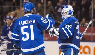Toronto Maple Leafs defenseman Jake Gardiner (51) congratulates goalie Curtis McElhinney (35) following their win over the Dallas Stars in NHL hockey action in Toronto on Tuesday, Feb. 7, 2017. (Frank Gunn/The Canadian Press via AP)