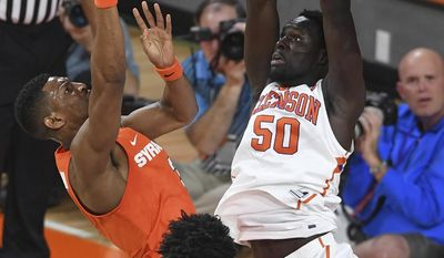 Syracuse guard Andrew White III, left, tries to score over Clemson center Sidy Djitte (50) during an NCAA college basketball game in Clemson, S.C., Tuesday, Feb. 7, 2017. (Bart Boatwright/The Greenville News via AP)