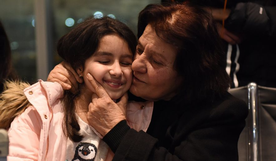 Kristina Halawi, 8, is kissed by her great aunt Sahira Jazrawi, 74, after her arrival at Detroit Metropolitan Airport Tuesday night, Feb. 7, 2017. Jazrawi along with her sister Suad Jazrawi, 77, were supposed to arrive last week but were delayed due to the executive order that stopped refugees from seven countries, including Iraq where they are originally from. A stay on the order was issued by a federal judge allowing the sisters, who have spent 5 years in Jordan waiting for asylum, to join their family in the U.S. (Tanya Moutzalias/The Ann Arbor News via AP)