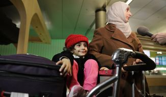 3-year-old Laila Alamri, of Yemen, sits on a cart while her mother, Samar Alwahiri, right, talks to reporters at Los Angeles International Airport Wednesday, Feb. 8, 2017, in Los Angeles. More than two dozen Yemenis who were stranded in Africa by President Donald Trump's travel ban have arrived Wednesday in Los Angeles. (AP Photo/Jae C. Hong)