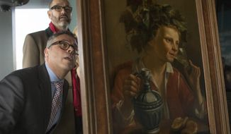 """Dr. Clarence Epstein, foreground, director of the Max Stern Art Restitution Project, inspects the back of """"Young Man As Bacchus"""" by Jan Franse Verzijl during a ceremony to formally return the painting to representatives of the Max and Iris Stern Foundation, Wednesday, Feb. 8, 2017, at the Museum of Jewish Heritage in New York. Federal investigators recovered the 1630 oil painting in a 2015 art fair. (AP Photo/Mary Altaffer)"""