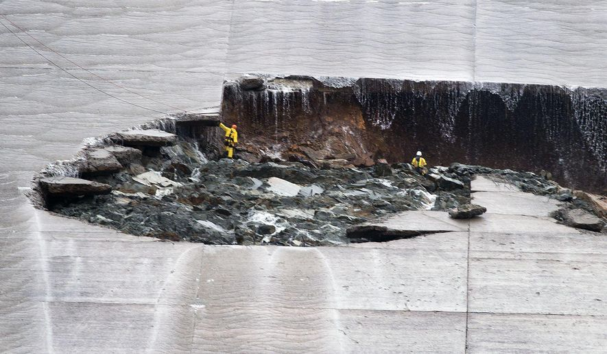 Water trickles down as workers inspect part of the Lake Oroville spillway failure on Wednesday, Feb. 8, 2017 in Oroville, Calif. The Department of Water Resources said the erosion at Lake Oroville does not pose a threat to the earthen dam or public safety, and the reservoir has plenty of capacity to handle the continuing rain. (Randy Pench/The Sacramento Bee via AP)