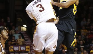 Iowa's Dom Uhl, right, of Germany, lays up as Minnesota's Jordan Murphy defends during the first half of an NCAA college basketball game Wednesday, Feb. 8, 2017, in Minneapolis. (AP Photo/Jim Mone)